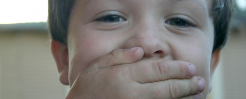 child with hand over mouth