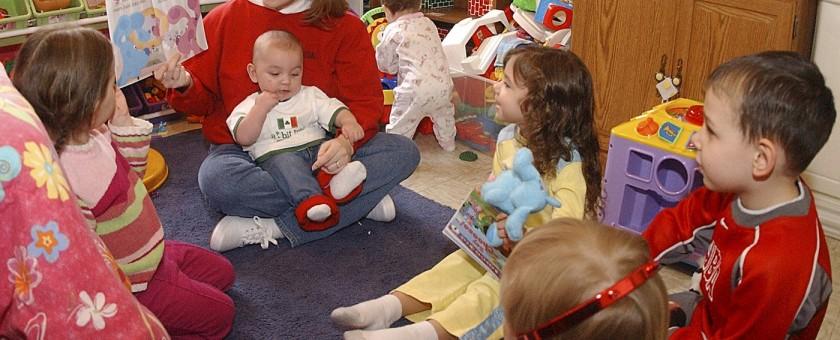 Nursery worker reading to children