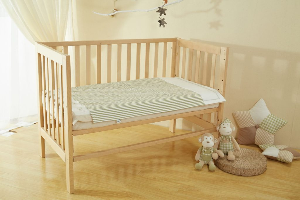 Wooden baby cot bed with teddys and cushions beside it on the ground