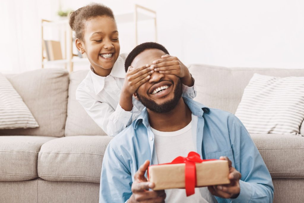 little girl giving her father a gift, a box tied with red ribbon