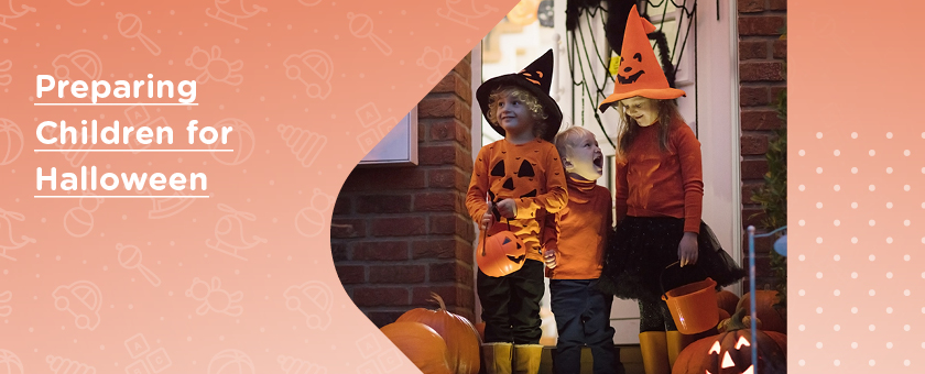 Three children dressed up as pumpkins who have gone out trick or treating for Halloween