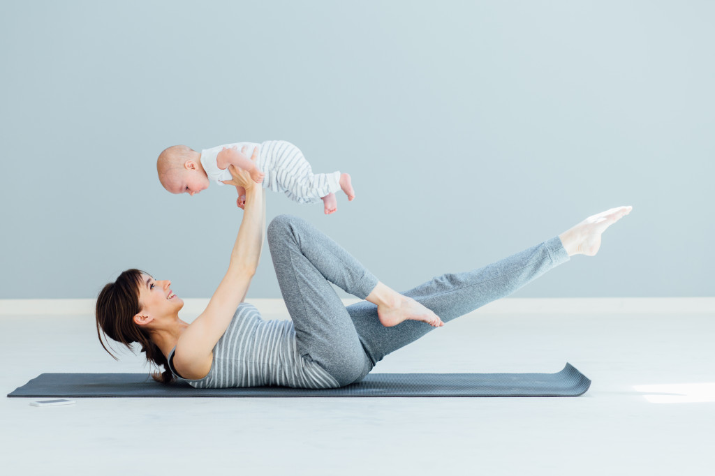 Mum and baby on a yoga mat in a yoga pose