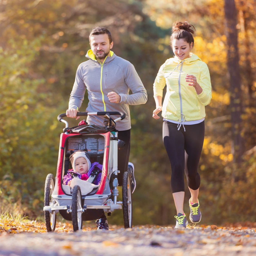 Man and woman running with a pushchair with a baby in it
