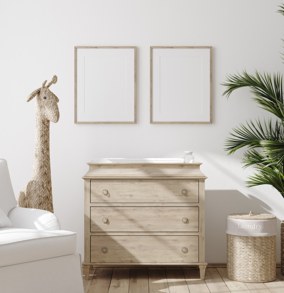 A neutral coloured nursery featuring a chest of drawers, a plant and a toy giraffe