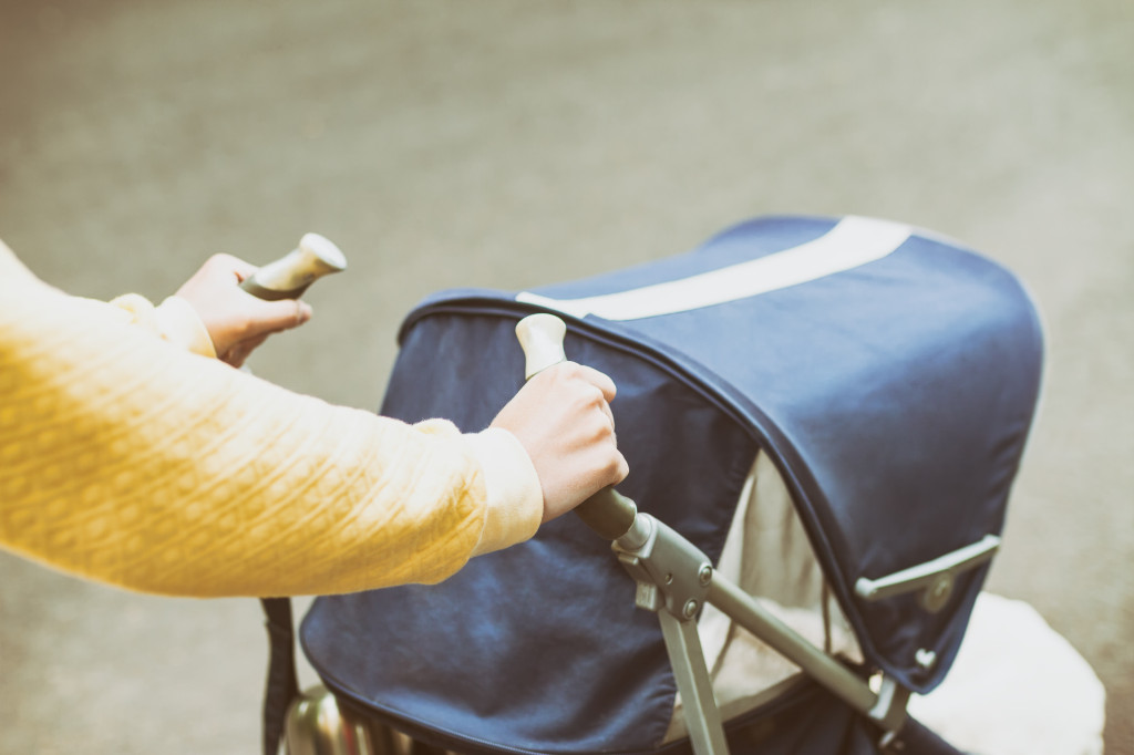 Birdseye view of a person's hands pushing a pushchair