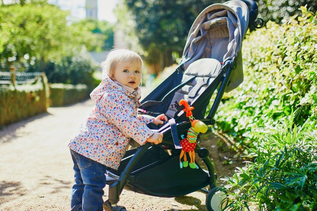 A blonde toddler stood up holding onto a pushchair and looking to the camera