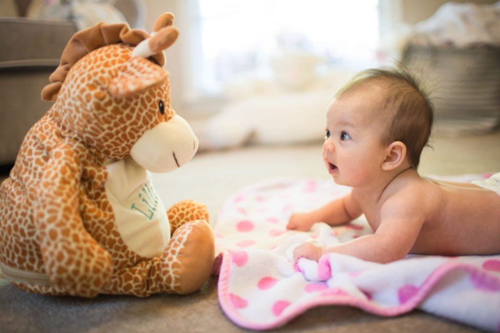 Baby on tummy looking at a teddy