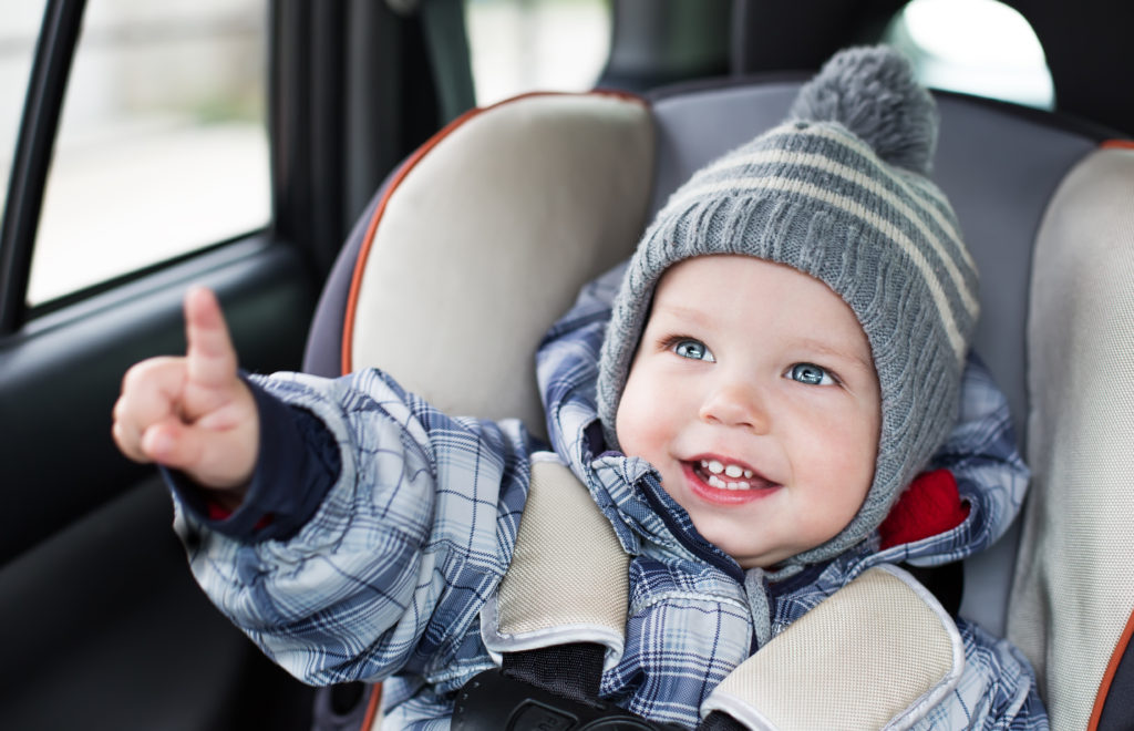 Happy baby in a car seat, pointing at the camera