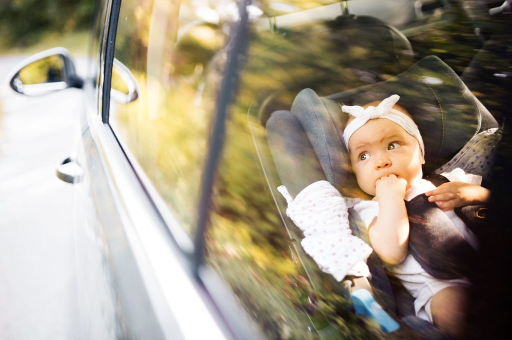 Newborn baby in a rear facing car seat, looking out of the car window