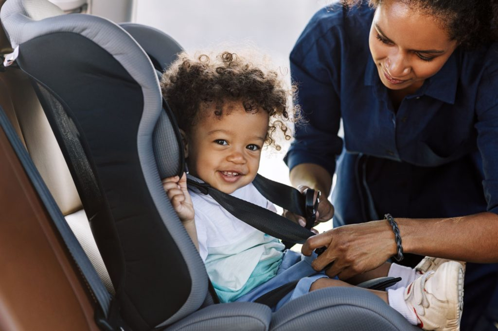 Happy child being strapped into a car seat by their mother