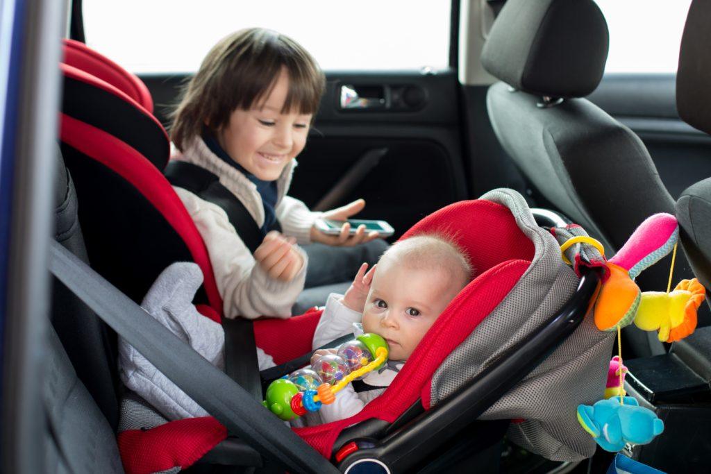 Newborn baby in a car seat looking at the camera, with their big brother looking at them smiling from their child seat