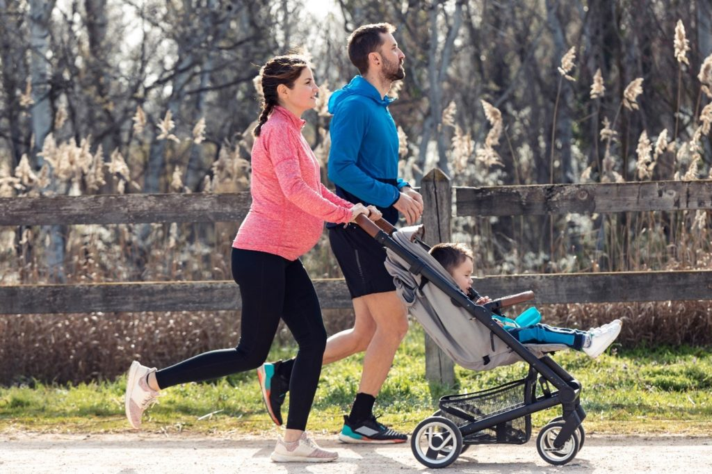 Mother and father jogging with baby in pushchair