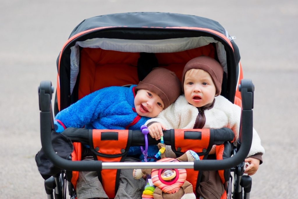 Twins cuddled up next to each other in double pushchair