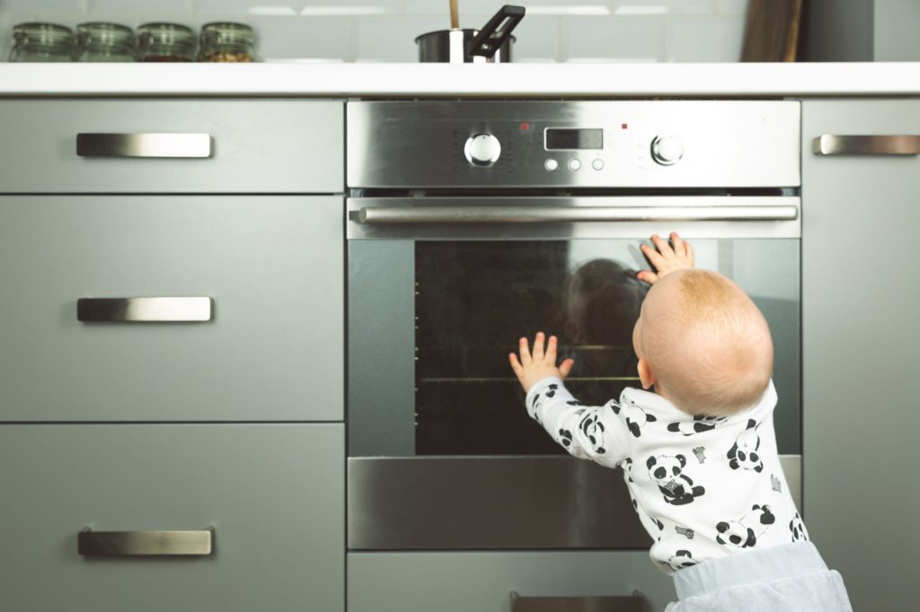 Snooping baby touching oven in kitchen