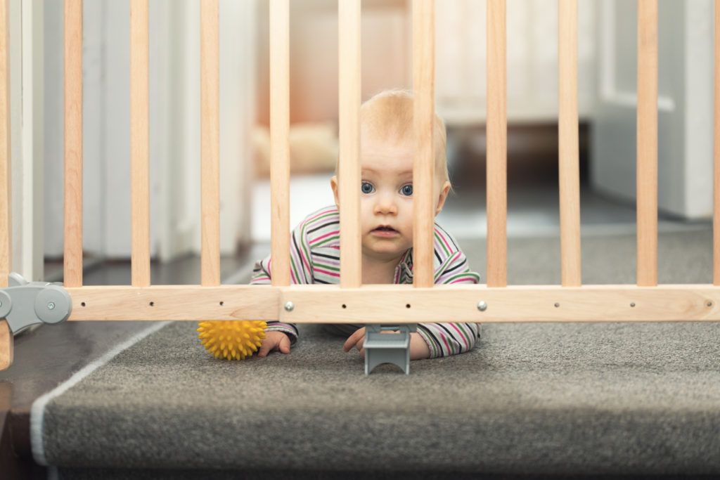 Baby laid behind stair gates with puppy dog eyes