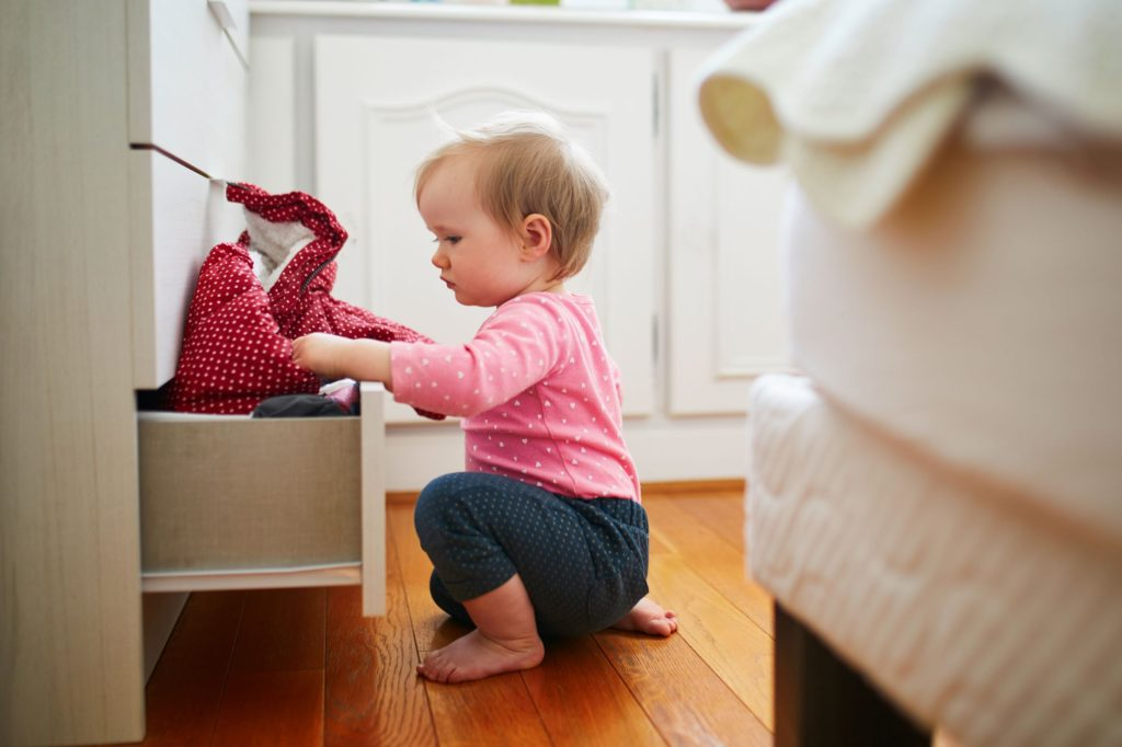 Tot snooping through clothes drawers