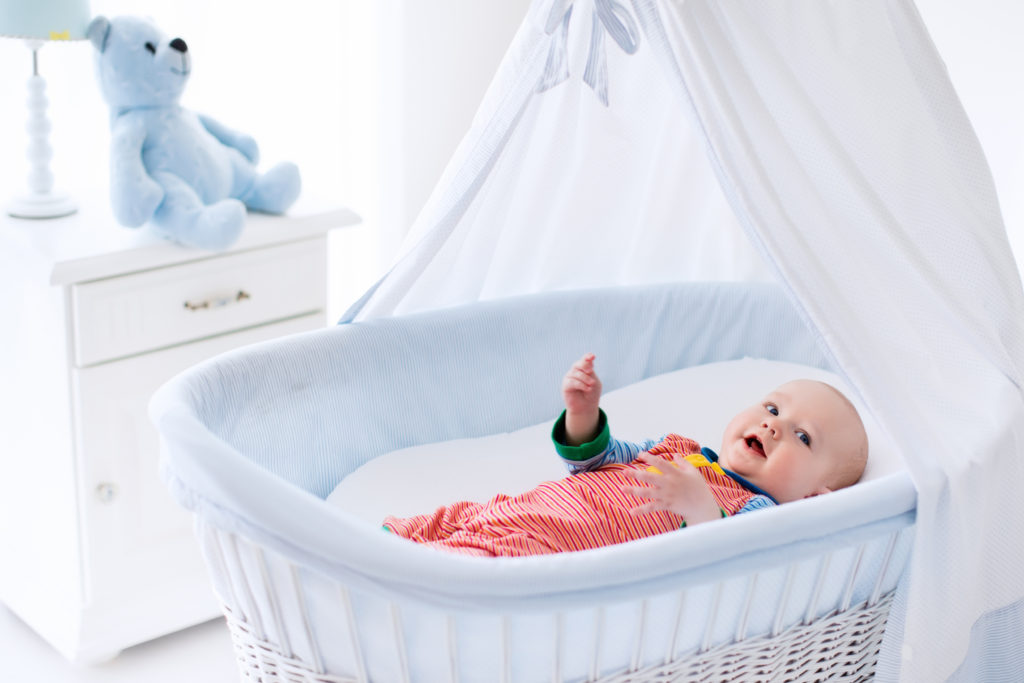 Baby smiling in Moses basket