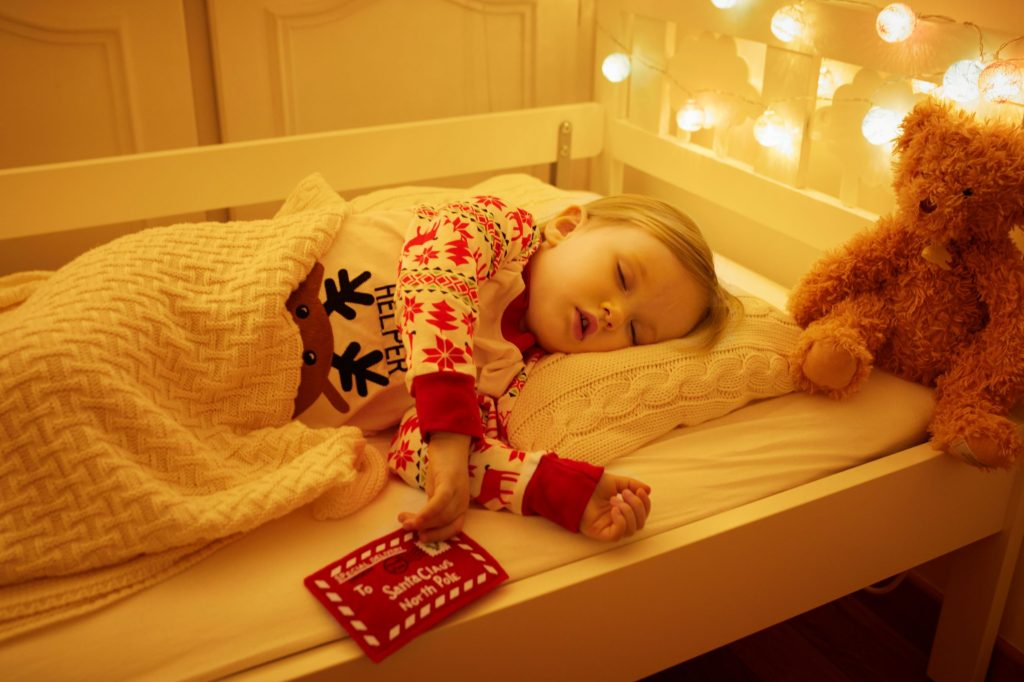 Tot sleeping in their bed next to their teddy