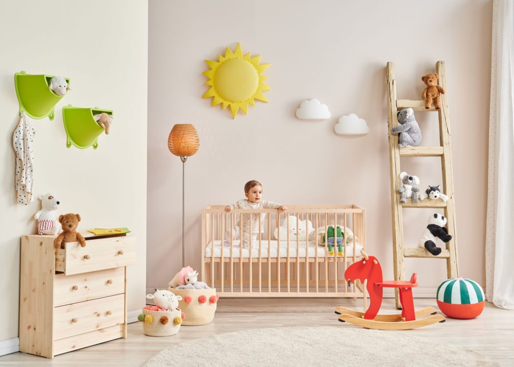 Baby kneeling in cot bed whilst surrounded by their beautiful nursery