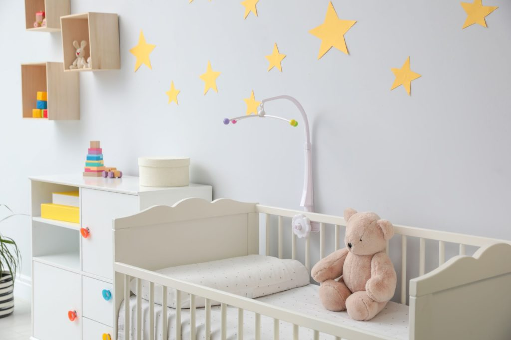 Stylish baby nursery with cot, teddy bear and stars on the wall