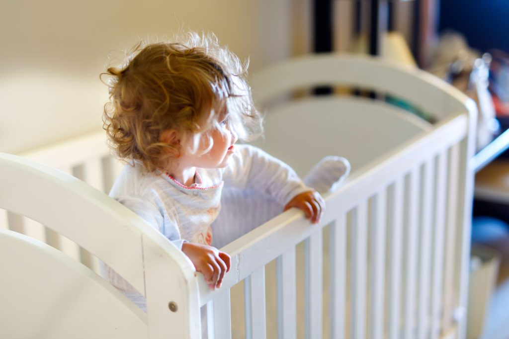 Baby with curly hair trying to climb out of cot
