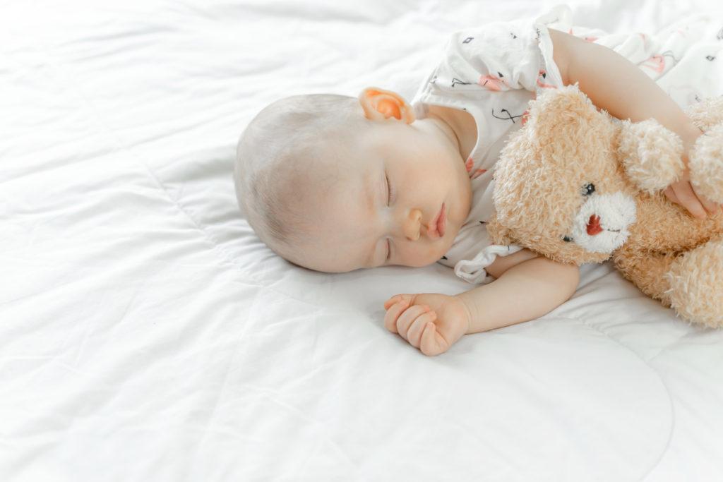Baby sleeping whilst cuddling cute teddy