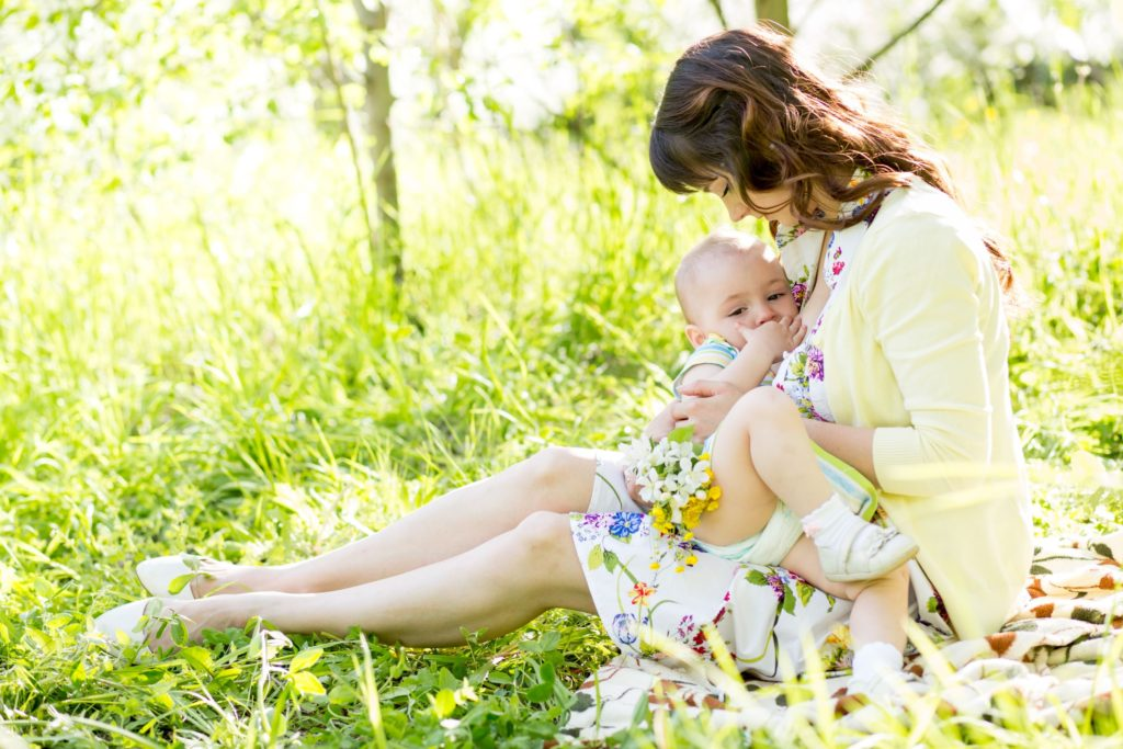 A mother breastfeeding her baby in a sunny field