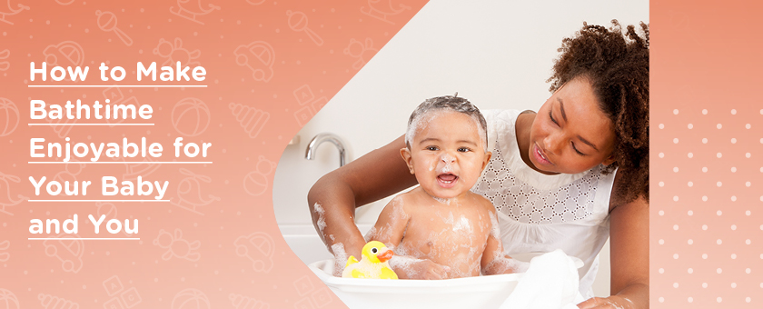 Happy baby with suds around their face being bathed by their mother