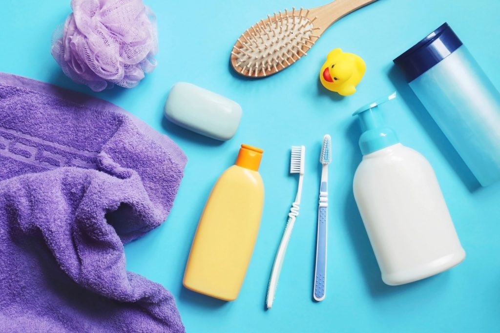 Bath time essentials such as lotion, rubber duck, hairbrush and towel
