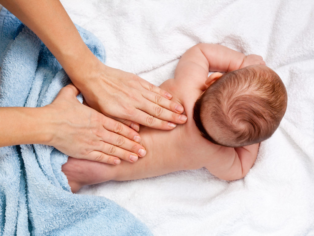 Baby being given massage by parent