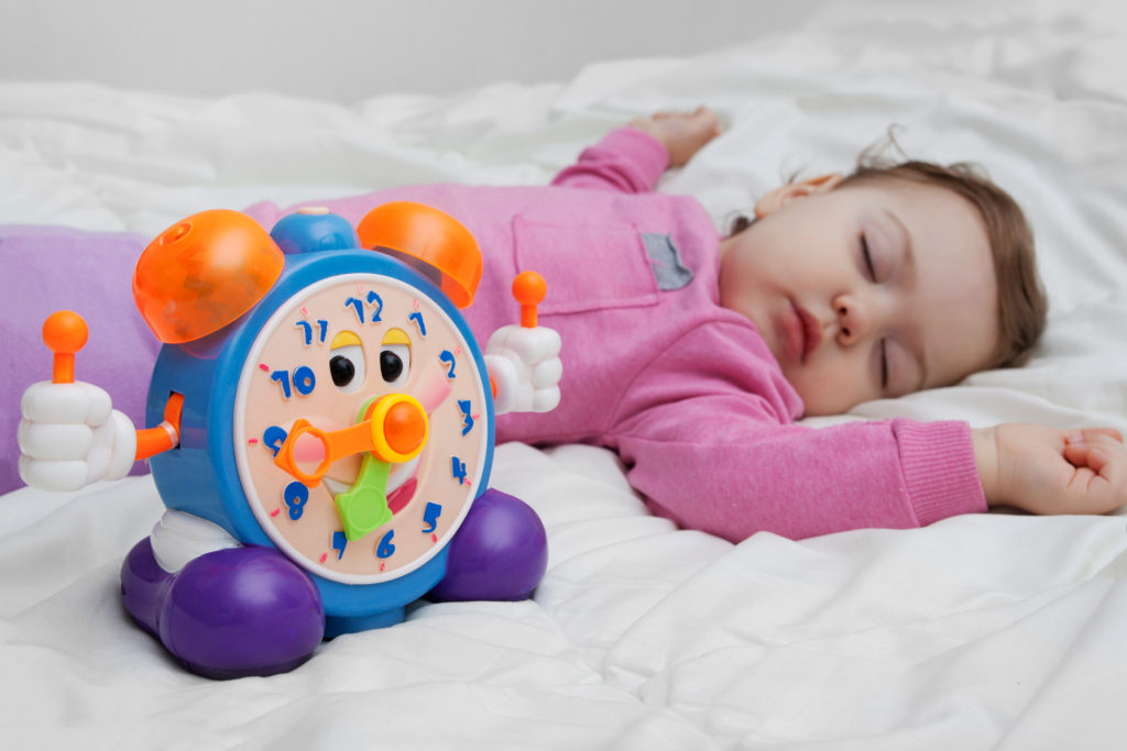 Baby sleeping with colourful toy alarm clock next to them