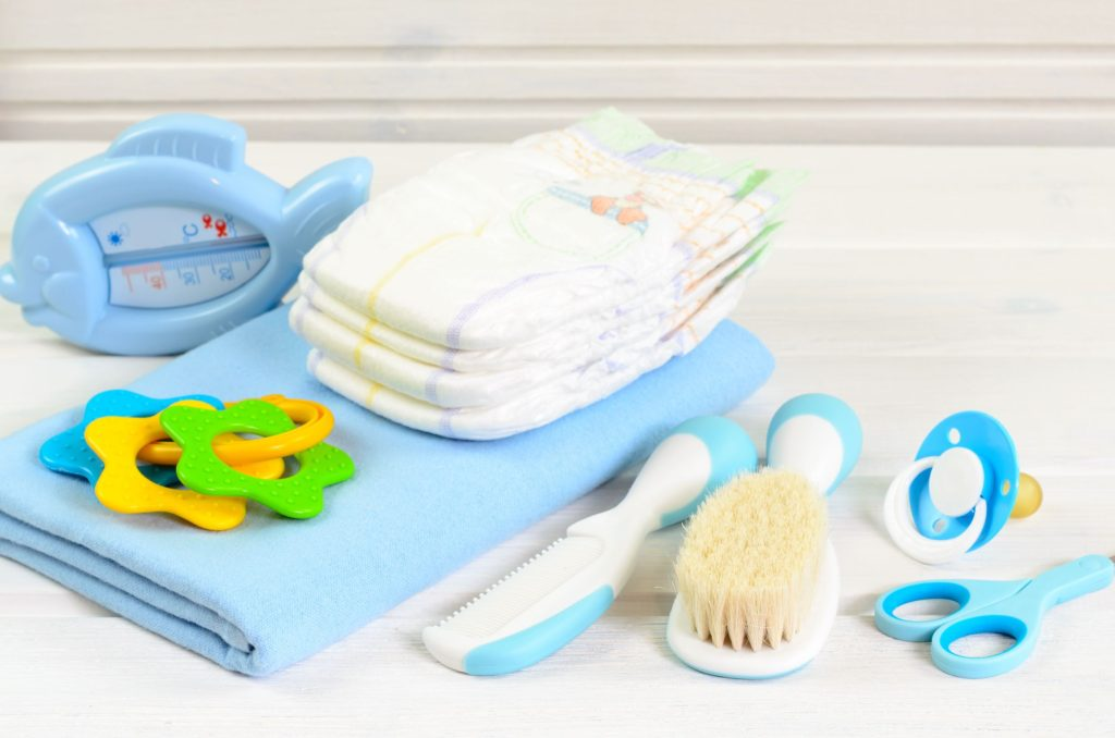 Baby bathing essentials such as thermometer, nappies, hairbrush, dummy, towel and toy