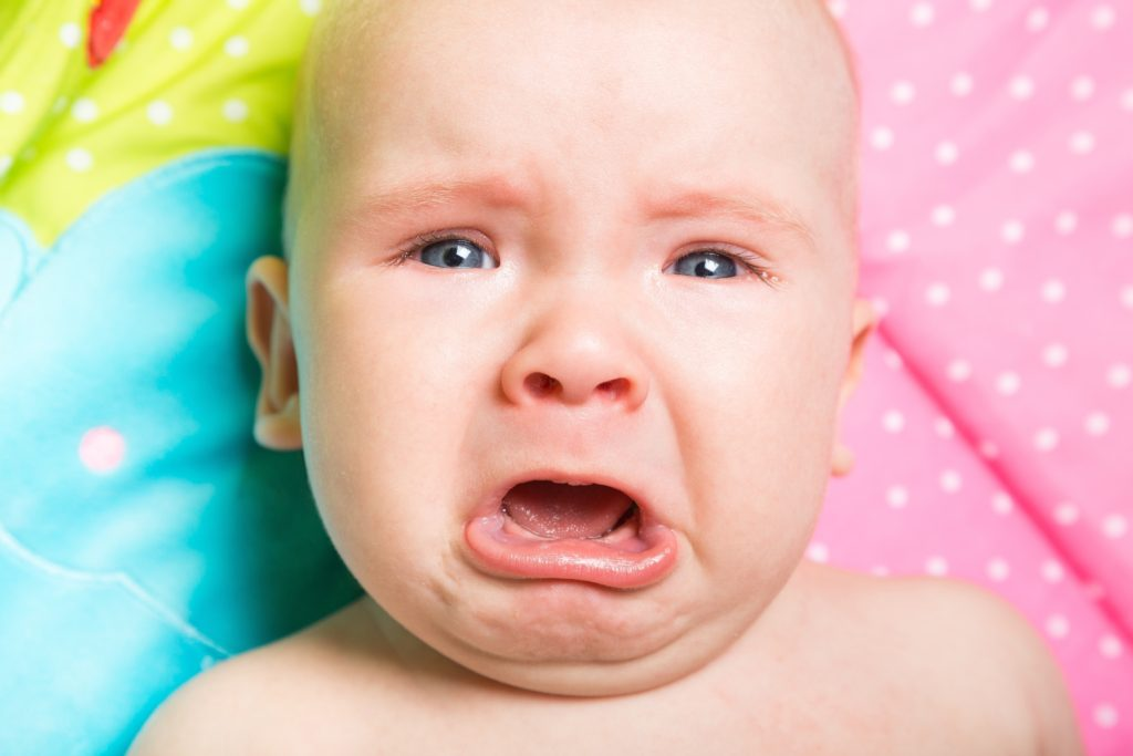 Baby on colourful bedding frowning and crying