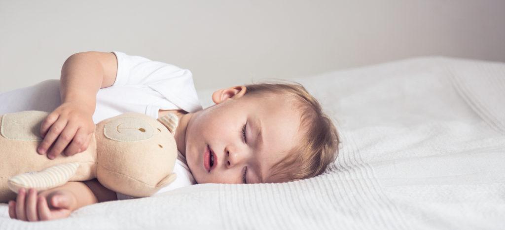 Baby sleeping whilst cuddling teddy