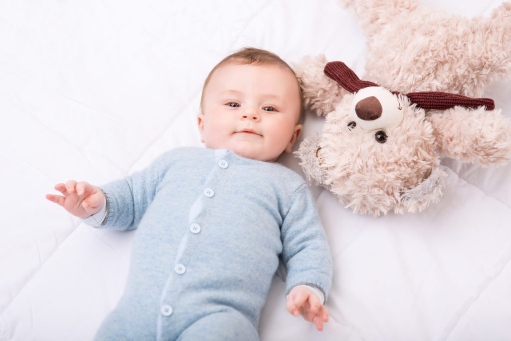 Baby in blue onesie looking into the camera with fluffy teddy lying the opposite way
